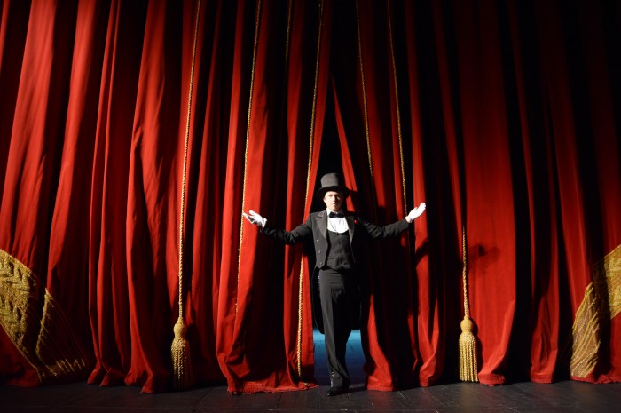 the actor in a tuxedo and hat opens the stage curtain